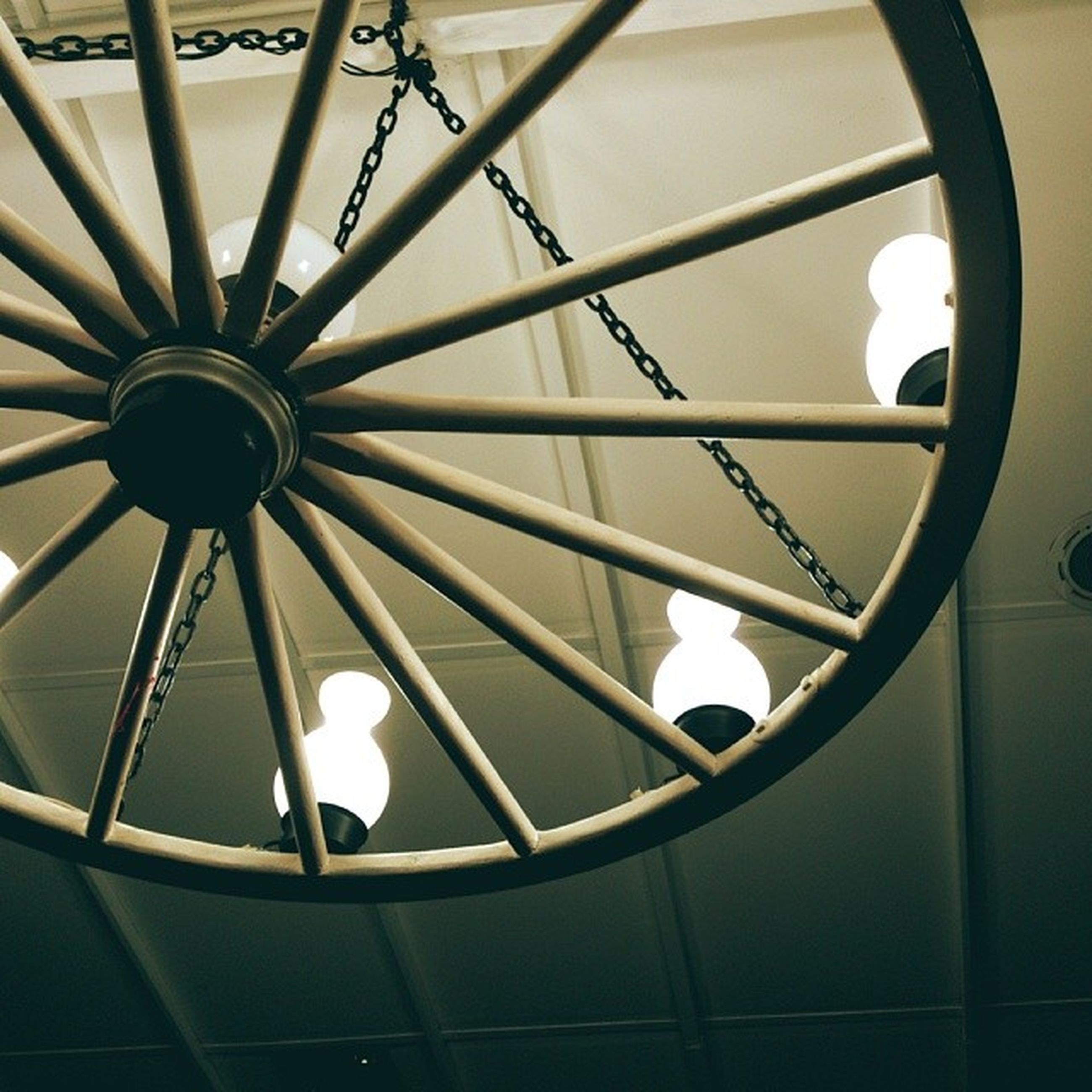 indoors, low angle view, ceiling, circle, directly below, geometric shape, built structure, pattern, lighting equipment, architecture, design, time, no people, illuminated, metal, hanging, clock, architectural feature, shape, skylight
