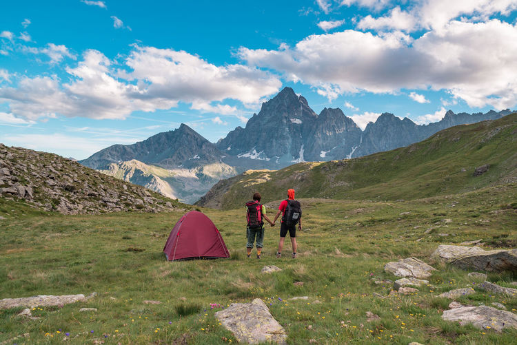 Couple looking at the majestic view of glowing mountain peaks at sunset high up on the Alps. Rear view with camping tent, focus in the background, toned and filtered image. Keywords: alps, couple, adventure, summer, tent, two people, mountain peak, camping, exploration, top, sunrise, sunset, looking at view, discovery, hiking, trekking, majestic, 3000 meter, above, resting, rock, high up, aspirations, landscape, horizon, rear view, valley, wilderness area, extreme terrain, glowing, relaxation, mountain, panoramic, remote, mountain range, rocky mountains, solitude, scenics, loneliness, silence, idyllic, Outdoors, Nature, canada, usa, italy, switzerland, wide angle Beauty In Nature Day Mountain Mountain Range Nature Outdoors Scenics Sky