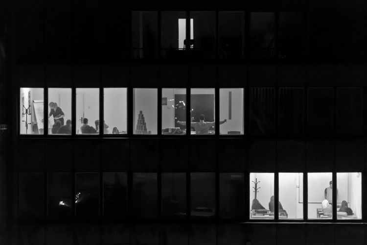 People in building seen through windows at night
