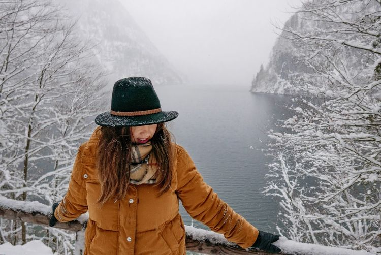 Woman standing against sea during winter