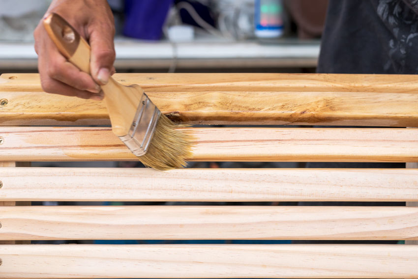 Young man's hand holding a brush applying varnish paint on a wooden furniture Close-up Day Focus On Foreground Hand Holding Human Body Part Human Hand Indoors  Men Occupation One Person Plank Preparation  Real People Skill  Unrecognizable Person Wood - Material Working Workshop