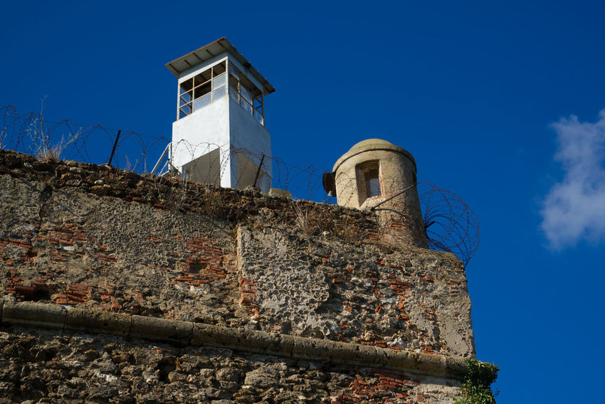 A detail of the maximum security prison sight tower Barbed Wire Castle Elba Island  Prisoner Tuscany Wall Blue Blue Sky Elba Fortress Fortress Wall Guard Italy Maximum Maximum Security Maximum Security Prison Prison Sight Tower Sky Stone Wall Supermax Supermax Prison War Stories From The City