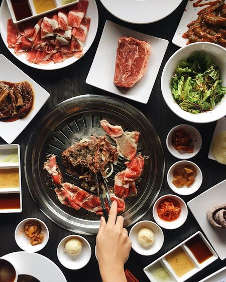 High angle view of hand holding food over hotpot on table