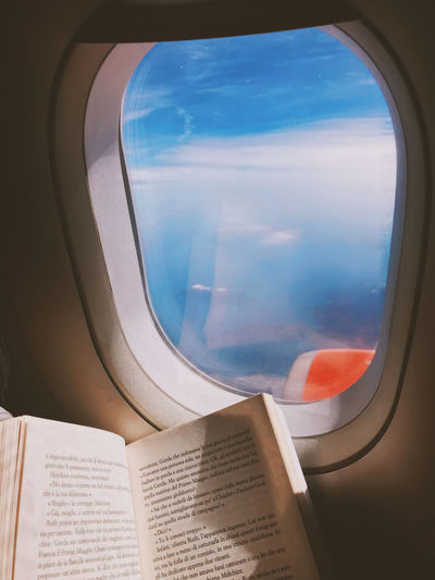 View of airplane window Air Vehicle Airplane Book Flying Glass - Material Indoors  Journey Mode Of Transportation Motion Newspaper No People Paper Public Transportation Publication Reading Transparent Transportation Travel Vehicle Interior Window