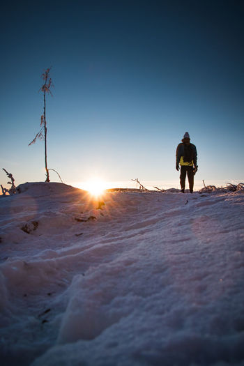 Rear view of man on snow covered land against sky during sunset