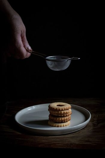 Close-up of hand holding sieve over cookies in plate on table