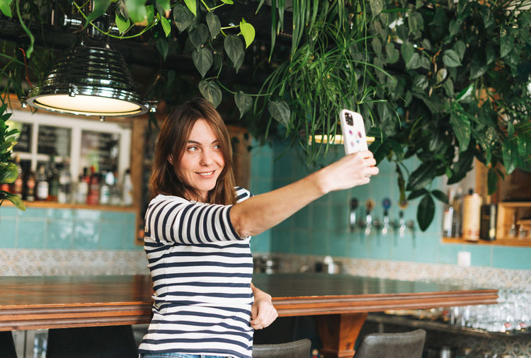 Portrait of young woman using phone while standing outdoors