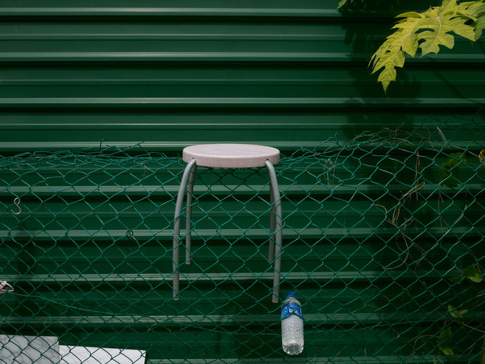 Close-up of table on chainlink fence