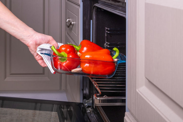 Person holding red bell peppers at home