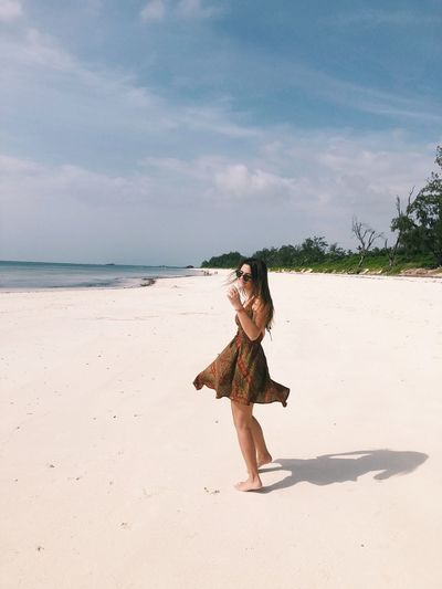 Side view of young woman standing at beach