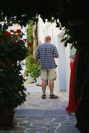 Rear view of man standing on footpath