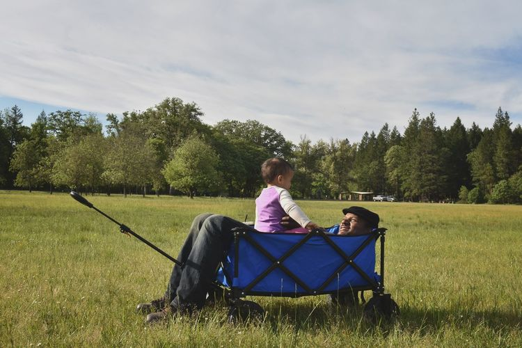 Father and daughter in cart on grass against trees and sky