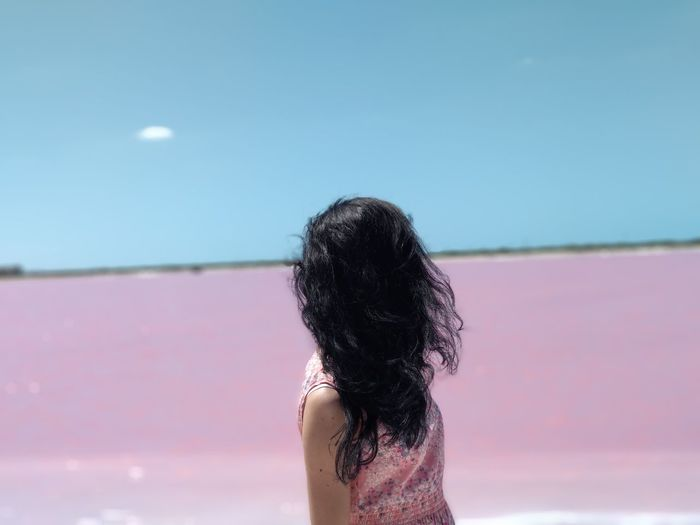 Rear view of woman against pink lake against sky