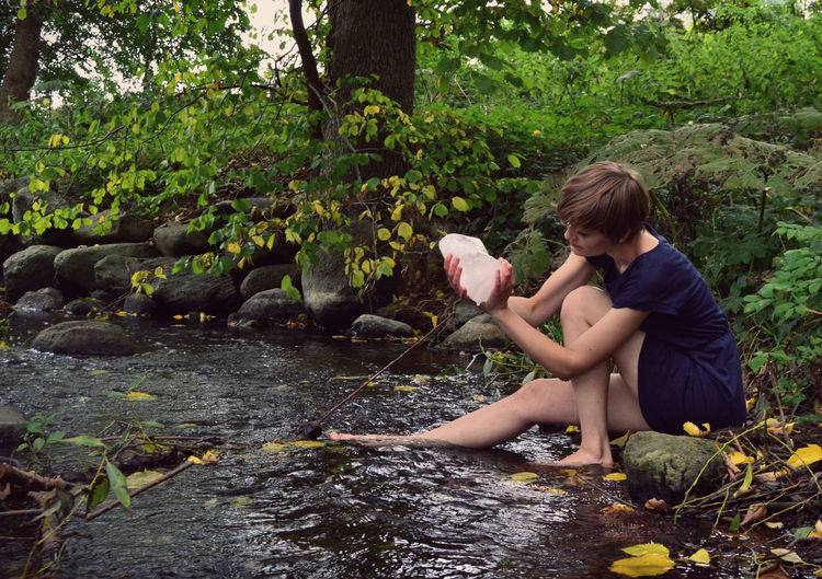 Young Woman Holding Ice While Sitting By Stream In Forest