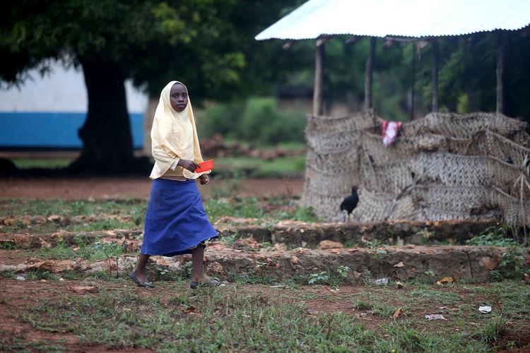 Woman with umbrella walking on field