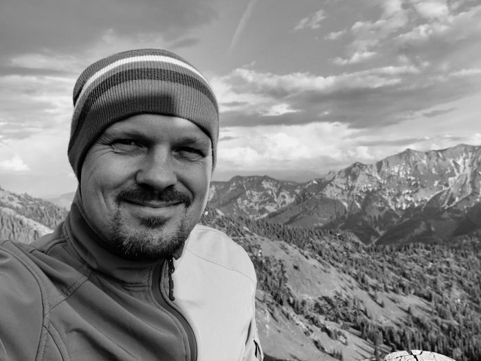 Portrait Mountain Smiling Looking At Camera Headshot One Person This Is My Skin Leisure Activity Real People Lifestyles Mountain Range Front View Happiness Sky Men Nature Adult Males  Mature Men Beauty In Nature Cloud - Sky This Is My Skin Adult Hat Warm Clothing Happiness Nature Clothing Looking At Camera