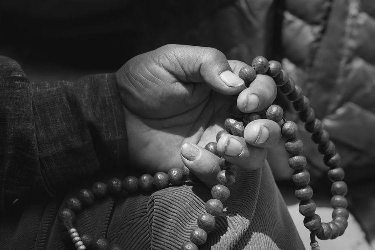 Cropped hand holding prayer beads