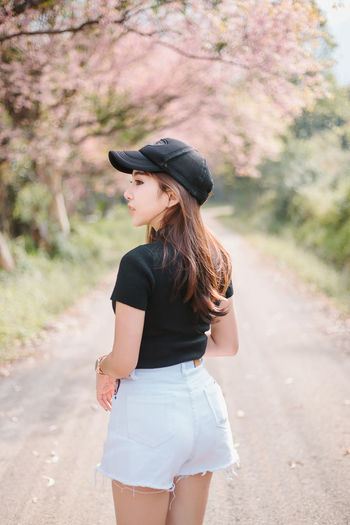 Young woman looking away while standing on road