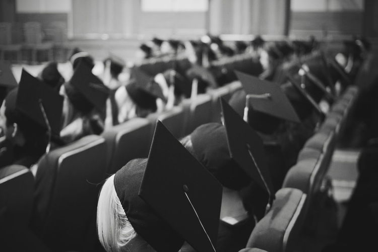 Students Wearing Mortarboards While Sitting In Auditorium