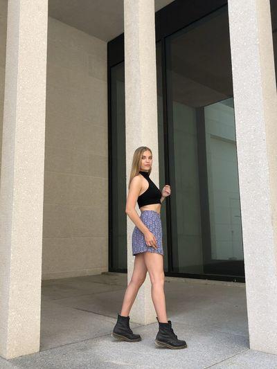Full length portrait of teenage girl standing against building