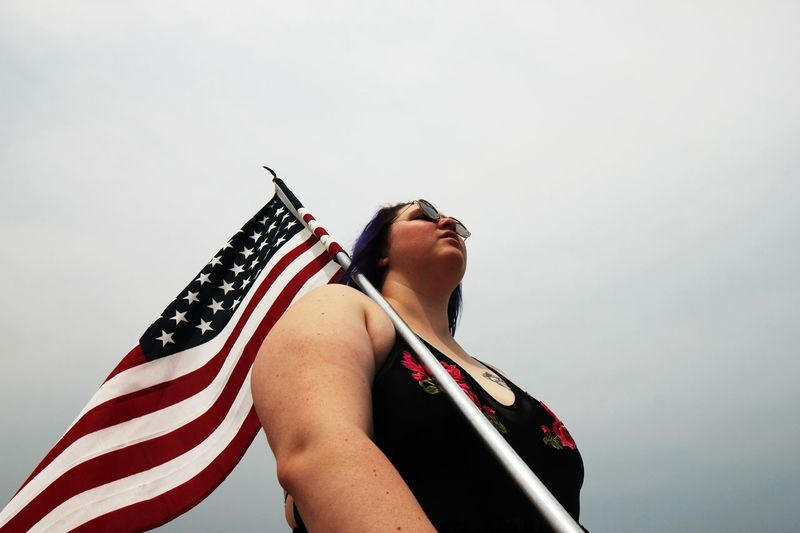 Woman in a bathing suits with the American flag on her shoulder 4th Of July EyeEm Selects One Person Sky Flag Real People Striped Lifestyles Leisure Activity Women Low Angle View Copy Space Fashion Young Adult Day Young Women Nature Glasses Patriotism Sunglasses Outdoors Beautiful Woman