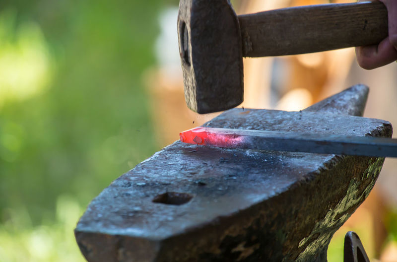 Close-up of metal and hammer on anvil at workshop