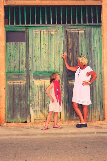 Girl looking at grandmother while standing on footpath