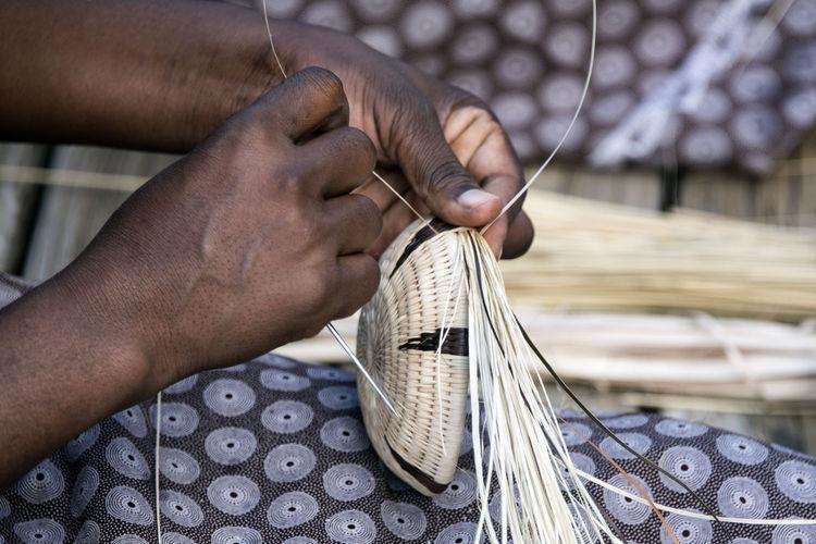 Cropped hands of worker making wicker basket in workshop