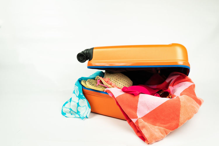 suitcase filled with vacation stuff Studio Shot White Background Still Life Indoors  Group Of Objects Orange Color Variation Suitcase Holiday Beach Towel Hat Slippers Sunglasses Bikini Scarf Trolley Copy Space Cut Out Citytrip