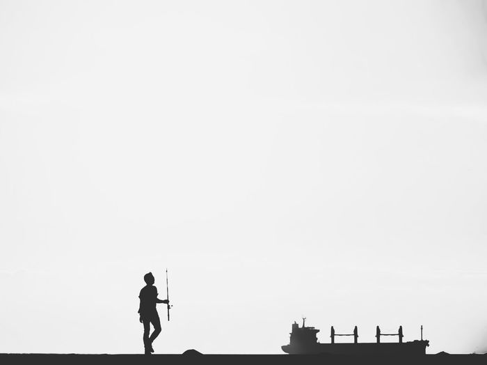 Silhouette man standing on building against clear sky