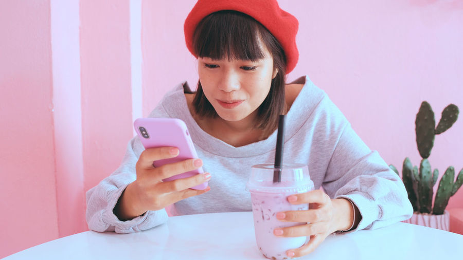 Young woman using mobile phone while having drink at table