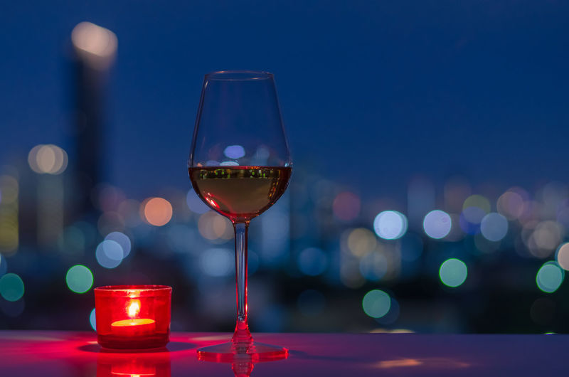 Close-up of wine glass on table at night