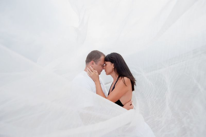 Couple cuddling amidst white fabric