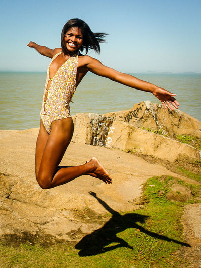Beach Beauty In Nature BlackWoman Girl Happiness Happiness Jumping Looking At Camera Nature One Person Openarms Outdoors Real People Scenics Sea Smile Smiling Water Young Adult Young Women
