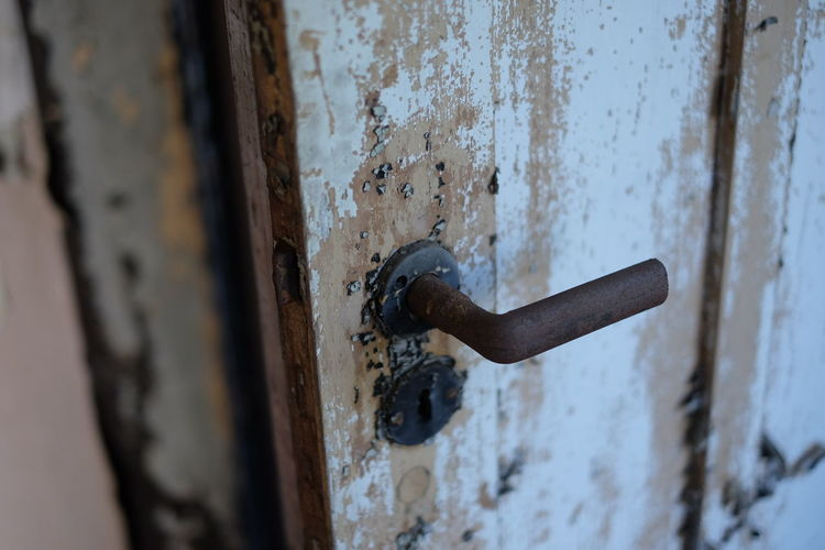 Close-Up Of Rusty Doorknob On Weathered Door
