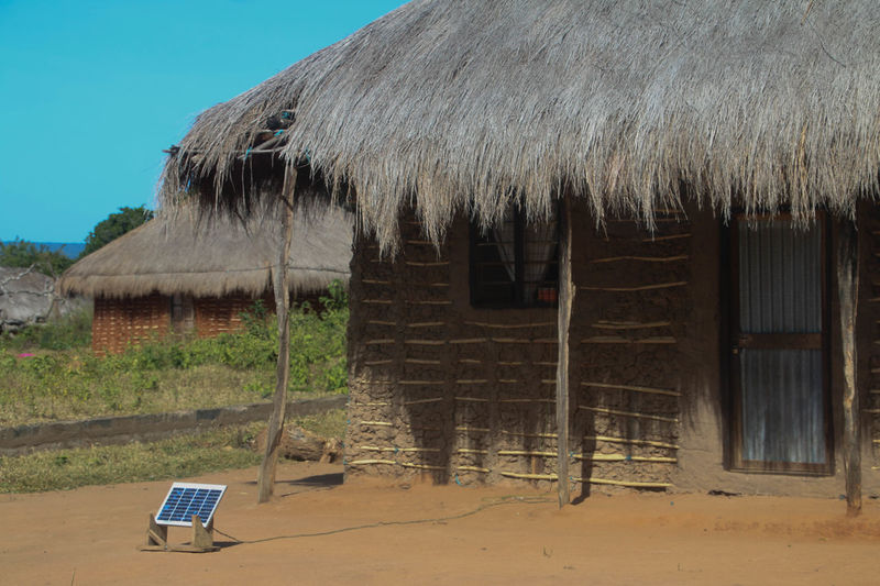 A mud house with a solar panel for lights and charging cell phones Animal Themes Architecture Building Exterior Built Structure Charging My Phone Charging Station Day Electricity  Mammal Mud Hut Mud Huts Nature No People Outdoors Rural Scene Sky Solar Panel Thatched House Thatched Roof