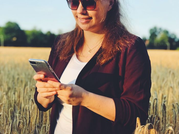 Woman using mobile phone while standing on field