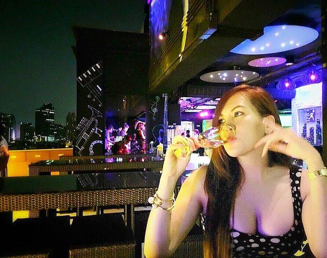 Woman in illuminated city at night