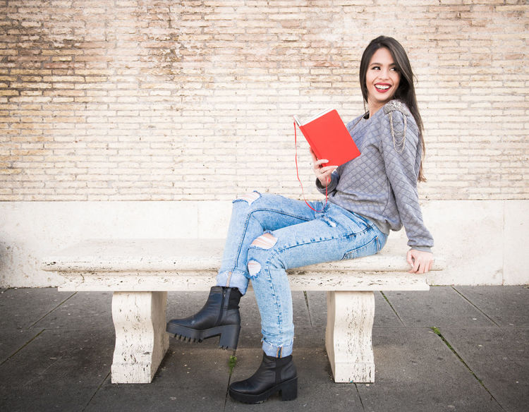 Young latina woman reading red book Bench Looking Out Red Book Woman Latina Woman One Young Woman Only Reading A Book Relax Smiling Travelguide Young Women