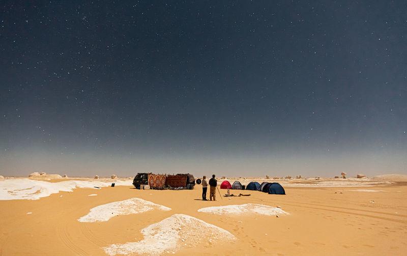 People on desert against sky