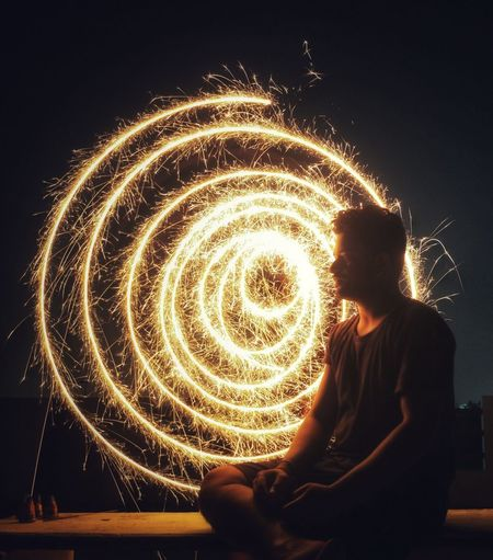 Man Sitting Against Sparkler At Night