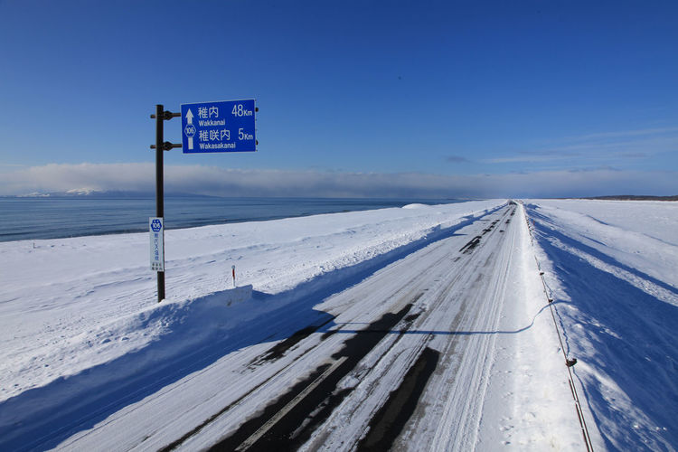 landscape japan hokkaido sarobetsu Beauty In Nature Blue Cold Temperature Communication Day Guidance Information Information Sign Nature No People Road Road Sign Sign Sky Snow Snowcapped Mountain Text Western Script White Color Winter