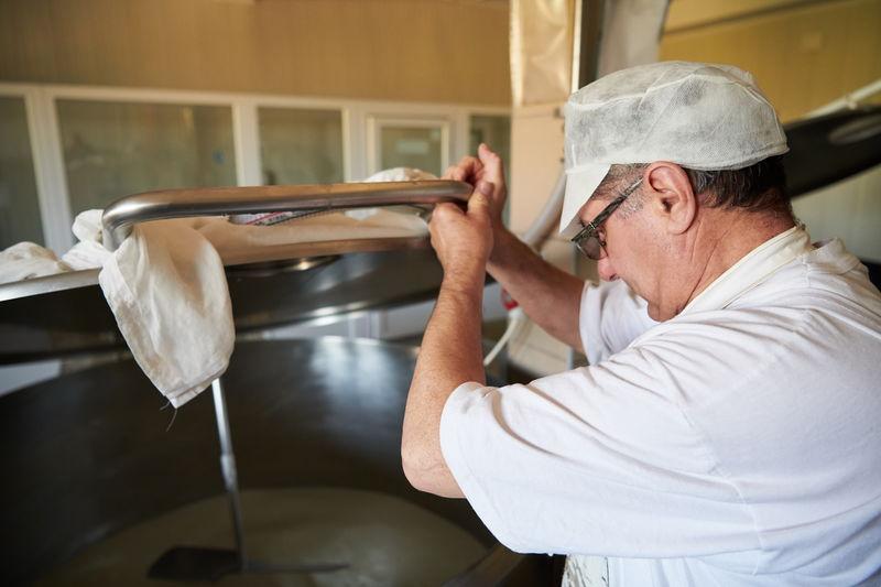 Side view of man preparing food in kitchen