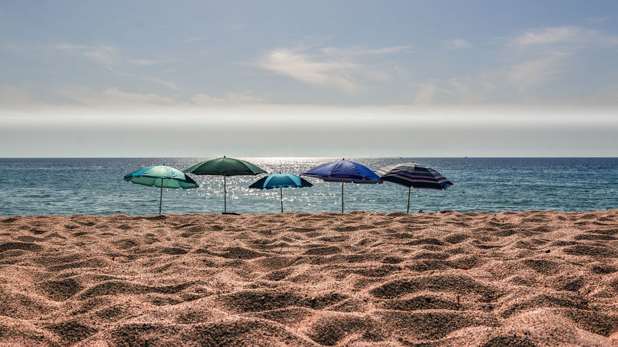 Colorful Parasols At Beach Against Sky