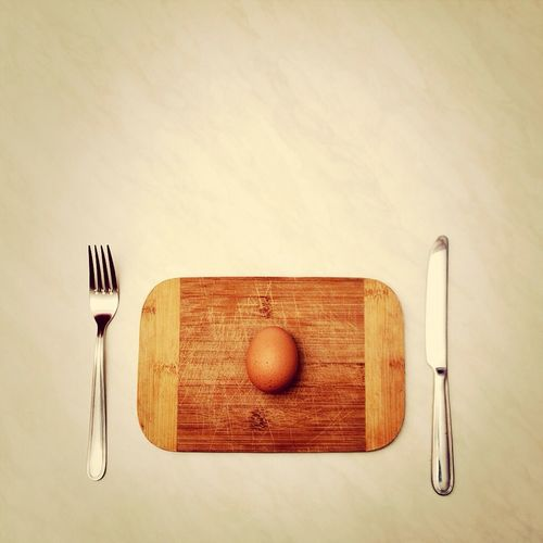 Close-up of egg on wooden plate served on table