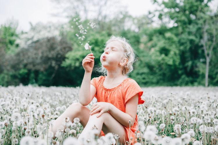 Full length of girl holding flower on field
