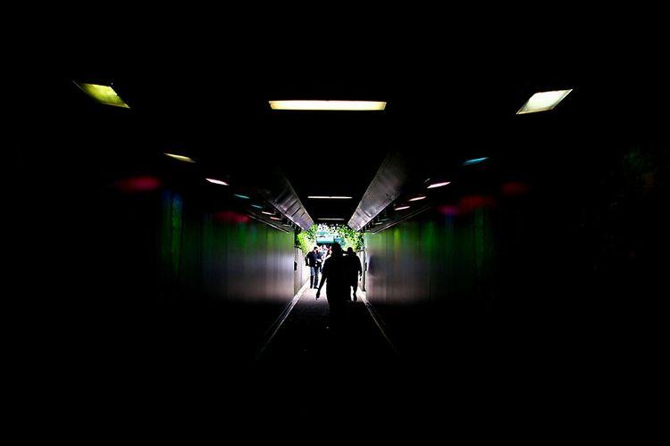Silhouette man in illuminated tunnel