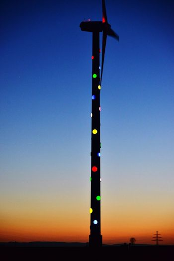 Low angle view of illuminated lights against clear sky at sunset