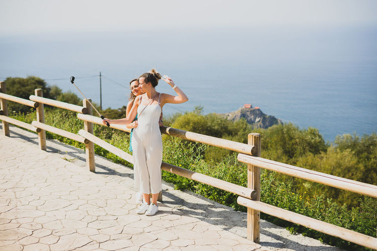 Women taking selfie while standing by railing against sea