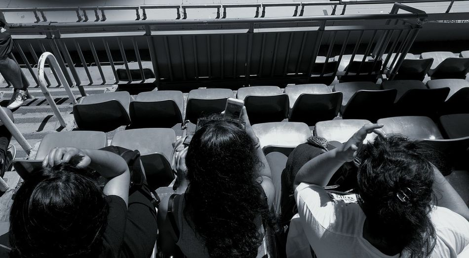 High Angle View Of Friends Sitting On Chair In Stadium